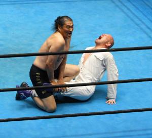 新井健一郎(右)に監獄固めを決める谷津嘉章