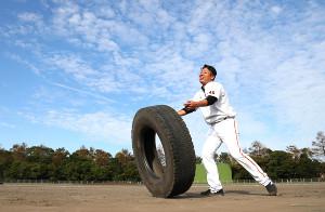 青空の下でタイヤを押すトレーニングをする今村