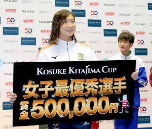 女子100M自由形決勝で52秒79の日本新記録をマークした池江璃花子は女子最優秀選手賞も獲得しボードを手に笑顔