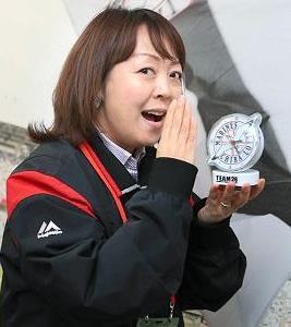 ファンクラブゴールド会員入会記念特典の「音声付き目覚まし時計」を持つアナウンス担当の谷保恵美さん