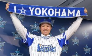 入団会見で球団の応援タオルを大きく掲げ笑顔を見せる中井大介