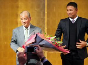 智弁和歌山の中谷監督(右)から花束を手渡され、笑顔を見せる高嶋名誉監督