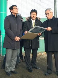 地震の被害のあった日高町営富川球場で説明に耳を傾ける栗山監督(左)