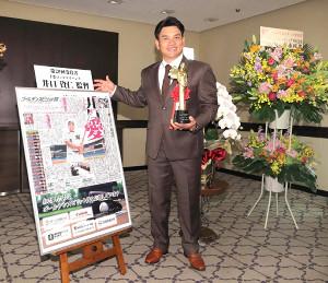 ゴールデンスピリット賞を受賞したロッテ・井口監督はトロフィーを手に本紙パネルの前で笑顔を見せる(カメラ・竜田 卓)