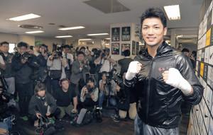 集まった大勢の報道陣の前でポーズをとる村田