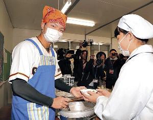 川辺小学校で給食の配膳を手伝う高田(カメラ・石田 順平)