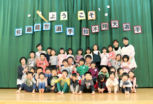 子供らと一緒に記念撮影する富士大・佐藤(中央左)と鈴木(中央右)
