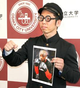 大みそかに世界初挑戦する大学院生ボクサーの坂本真宏は、王者ムザラネの写真を手に、学生服とだてメガネ姿で会見に臨んだ(カメラ・田村 龍一)