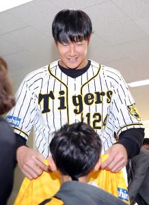 子どもにサイン入りユニホームを渡す阪神・横田