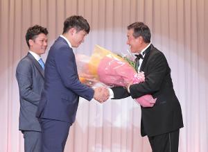 殿堂入りパーティーで花束を渡し、原監督とガッチリ握手する菅野(左手前、左奥は坂本勇、カメラ・橋口 真)