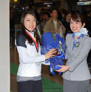 GPファイナルを終えてバンクーバーより帰国した紀平梨花(左)がANAの職員から花束をプレゼントされる