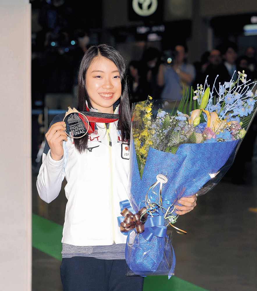 GPファイナルで優勝して帰国した紀平は、金メダルと花束を手に笑顔を見せた(カメラ・森田 俊弥)