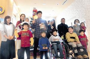 子供たちと記念写真を撮る銀次(左から5人目)