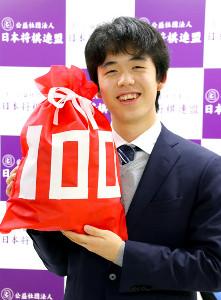「100」の文字が記されたクリスマスプレゼント袋を手に、笑顔を見せた藤井聡太七段