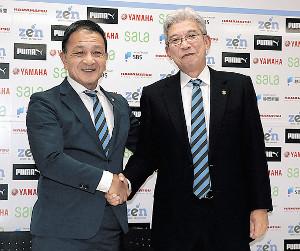 退任する木村社長と小野新社長(右)が握手