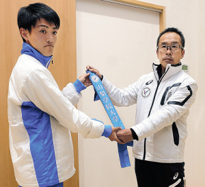 上田誠仁監督(右)から本番用のたすきを手渡される永戸聖主将