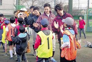 イベントに参加した少年らとハイタッチをかわす重信(右)と小島