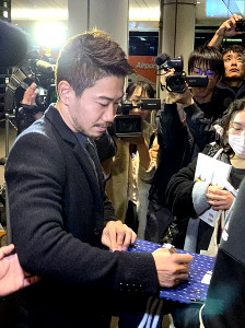 羽田空港に集まったファンにサインするドルトムントのMF香川真司