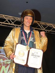 黄金のヘルメットをかぶりガッツポーズする峰竜太