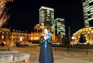 東京駅をバックにポーズを取る新田