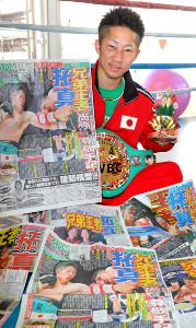 世界王者に就いた井上拓真は、スポーツ報知を手に喜びをかみしめた