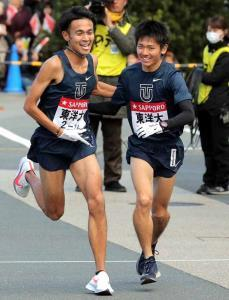 小田原中継所で4区の相沢晃(左)からタスキを受け取り走り出す、東洋大5区の田中龍誠