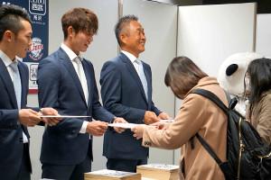 ファンにサイン色紙を手渡し、笑顔の辻発彦監督(中央)