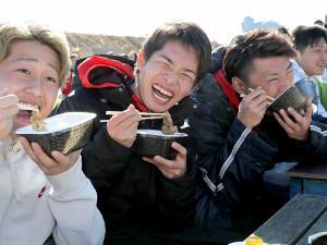 旧友と笑顔で牛丼を食べる高橋(中央)