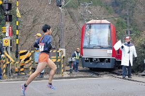 小涌谷踏切手前で停車した箱根登山鉄道の列車の前を通過する法大5区・青木(カメラ・杉山 彰一)