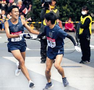 区間新記録の快走を見せた東洋大4区・相沢(左)は、トップで5区・田中にタスキをつないだ(カメラ・佐々木 清勝)