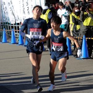 小田原中継所1位で通過する東洋大6区・今西駿介が、東洋大7区・小笹椋(右)にたすきを渡す