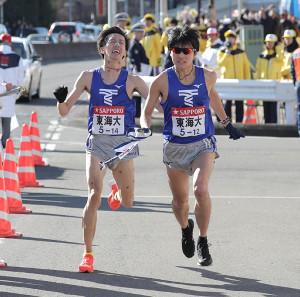 トップで8区・小松陽平からタスキを受ける東海大9区・湊谷春紀(右)