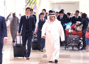 白い民族衣装の「トーブ」に身を包んだスタッフに誘導され、ドバイ空港に到着した大迫(左)ら日本代表イレブン(カメラ・竜田 卓)