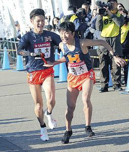 小田原中継所で法大6区・坪井(左)が、土井にタスキを渡す