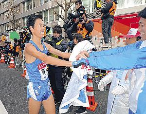総合8位でゴールし仲間に迎えられる順大10区の鈴木(左)