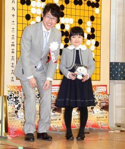 対局後、大盤の前で東大阪市のマスコットキャラクター「トライくん」のぬいぐるみを手に笑顔の仲邑菫さんと井山裕太5冠
