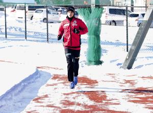 雪の積もるグラウンドをランニングするJ1札幌MF中野