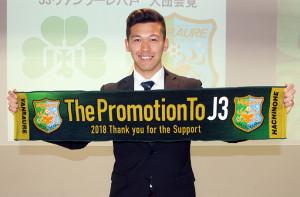 J3八戸のタオルマフラーを笑顔で掲げる仙台大GK金子