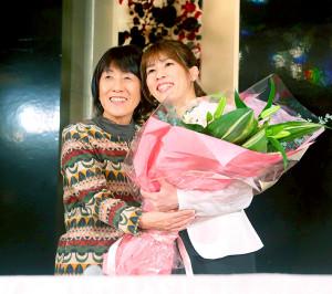 引退会見の最後に母・幸代さん(左)から花束を贈られ笑顔を見せる吉田沙保里さん(カメラ・矢口 亨)