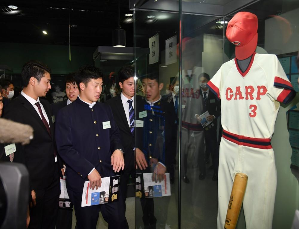 衣笠祥雄さんのユニホームなどを見学する小園海斗(前列左から2人目)(代表撮影)