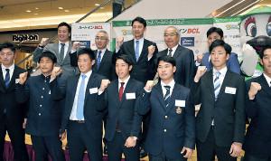 新入団選手とガッツポーズを見せる(後列左から)乾、永森社長、二岡監督ら