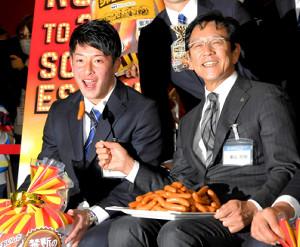 日本ハムグループの商品展示会で栗山監督(右)からソーセージを食べさせてもらう吉田輝(カメラ・今西 淳)