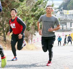 気合いの丸刈り姿で走り込む広島・中村奨成(右)