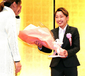 WBO女子アジアパシフィックミニマム級王者の佐伯霞は激励会で、姉の舞さんから花束を受け取り笑顔