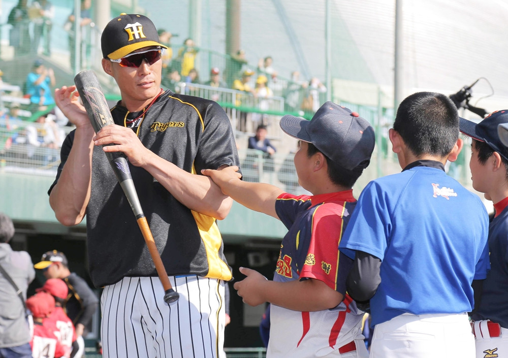 野球教室で子どもから筋肉を触られる阪神・糸井