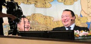 テレビの解説席で笑顔を見せる元稀勢の里の荒磯親方(左は芝田山親方=カメラ・相川 和寛)