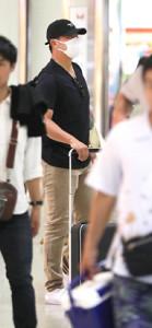 那覇空港で出発便の時刻表を眺める松坂(カメラ・渡辺 了文)