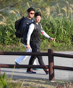 歩いて球場に向かう吉田輝星。左は柿木