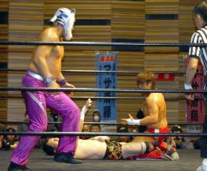 マサ斎藤さんの巌流島幟の前で金本浩二に監獄固めを決める田中稔(左はスーパータイガー)