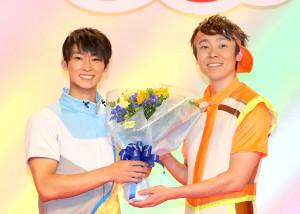 小林よしひさ(右)に花束を渡す福尾誠